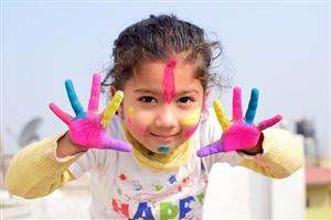 Smiling child with paint on her hands and face.
