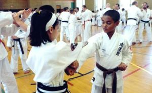 Young Boy and Girl Sparring in Karate